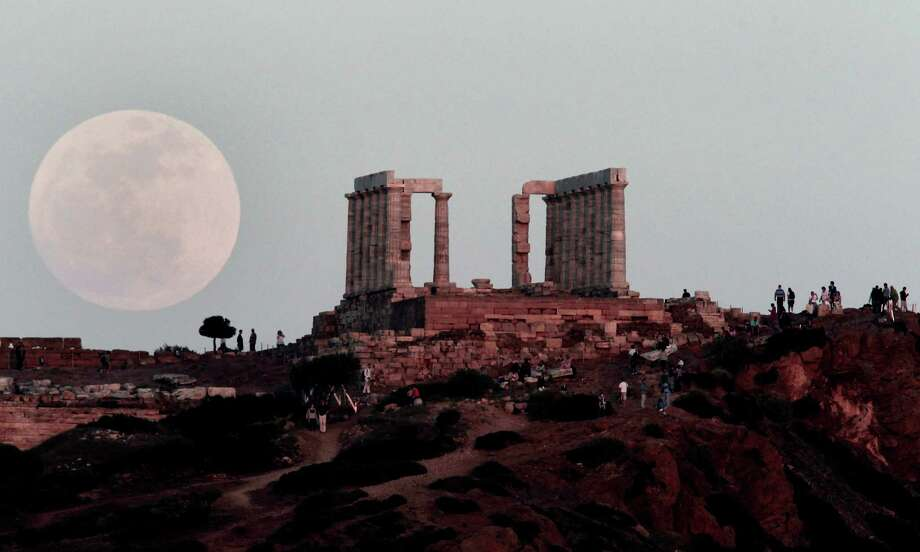 """The full moon rises behind the Temple of Poseidon in Cape Sounion, south east of Athens, Greece, while tourists watch, on Saturday, May 5, 2012.  Saturday's event is a """"supermoon,"""" the closest and therefore the biggest and brightest full moon of the year. (AP Photo/Dimitri Messinis) Photo: Dimitri Messinis, Associated Press / AP"""