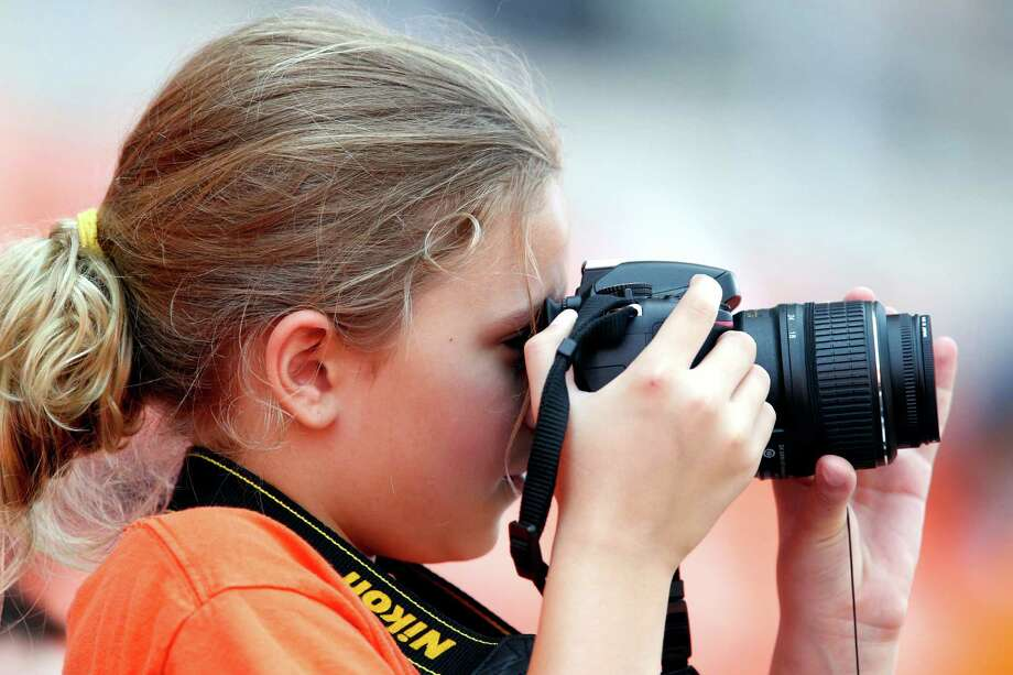 Eight-year-old Caroline Freyre takes a photograph during the Houston Dynamo soccer team practice at BBVA Compass Stadium Saturday, May 5, 2012, in Houston. Photo: James Nielsen, Chronicle / © Houston Chronicle 2012