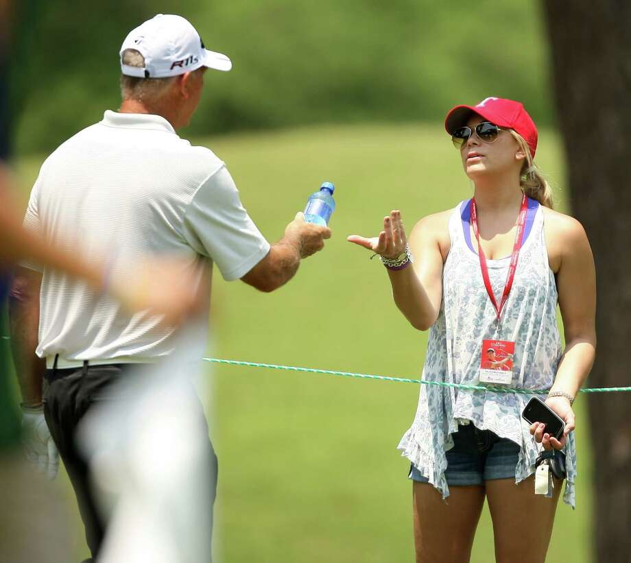 Tom Lehman hands daughter Rachael a bottle of water on the No. 5 fairway during the second round of the Insperity Championship, Saturday, May 5, 2012 at the Tournament Course in The Woodlands, TX. Photo: Eric Christian Smith, For The Chronicle