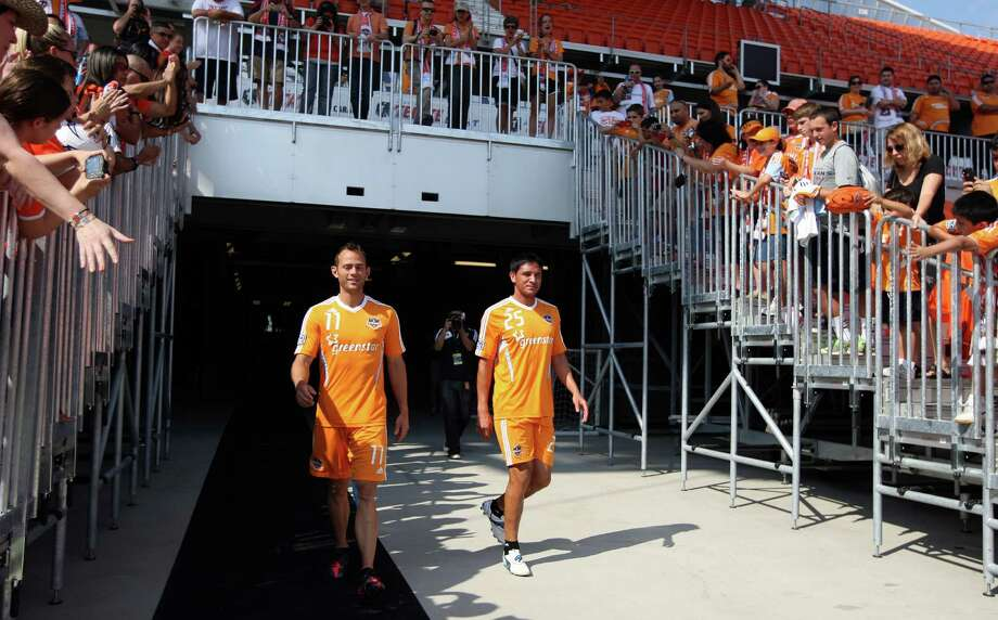 The Houston Dynamo's Brad Davis left, and Brian Ching walk on to the field before the Houston Dynamo soccer team practice at BBVA Compass Stadium Saturday, May 5, 2012, in Houston. Photo: James Nielsen, Chronicle / © Houston Chronicle 2012