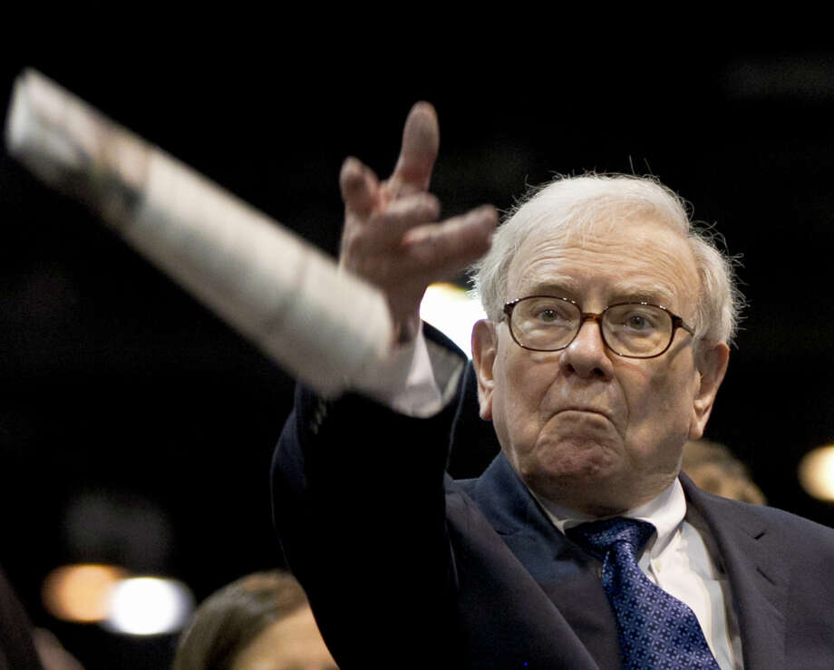 Warren Buffett, chairman and CEO of Berkshire Hathaway attempts to win the newspaper tossing competition during Saturday's shareholders meeting. Photo: Nati Harnik