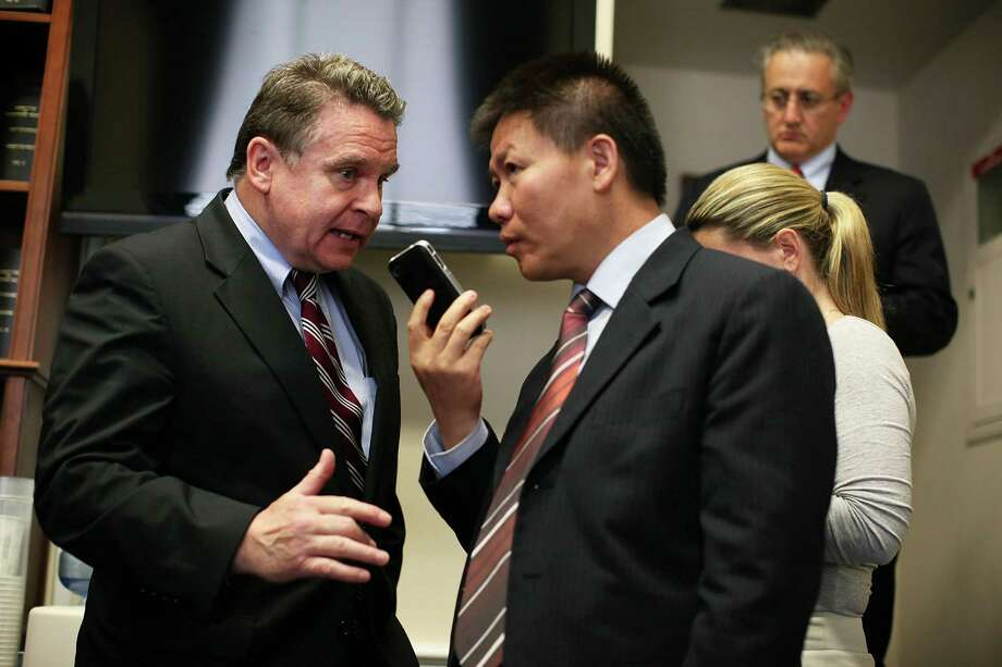 Bob Fu signals to U.S. Rep. Christopher Smith that he has gotten Chinese dissident lawyer Chen Guangcheng on his phone at Thursday's hearing. Photo: Alex Wong / 2012 Getty Images