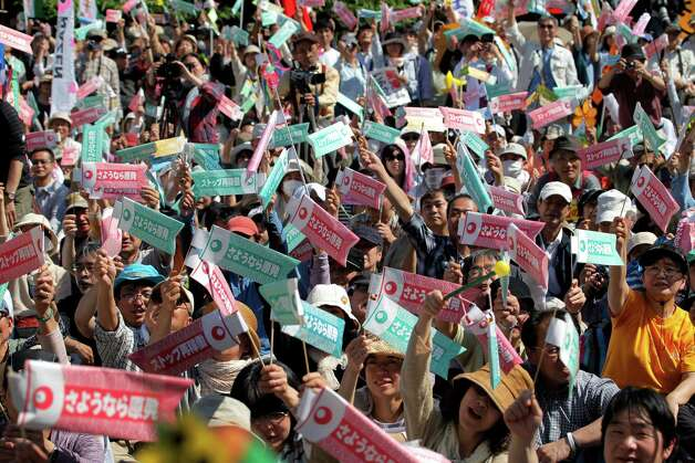 """Participants raise banners with a slogan, """"Good bye, nuclear power station"""", at a rally protesting against the usage of nuclear energy in Tokyo Saturday, May 5, 2012. Thousands of Japanese marched to celebrate the last of this nation's 50 nuclear reactors switching off Saturday, shaking banners shaped as giant fish that have become a potent anti-nuclear symbol. (AP Photo/Itsuo Inouye) Photo: Itsuo Inouye / AL"""