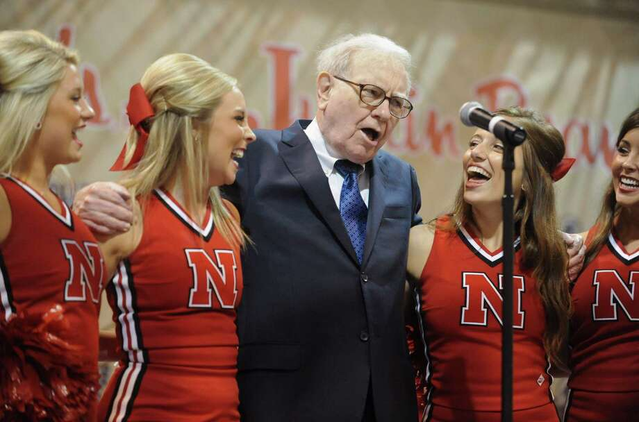 Warren Buffett, chairman and CEO of Berkshire Hathaway sings with University of Nebraska cheerleaders prior to the annual shareholders meeting in Omaha, Neb., Saturday, May 5, 2012. Berkshire Hathaway is holding it's annual shareholders meeting this weekend. (AP Photo/Dave Weaver) Photo: Dave Weaver