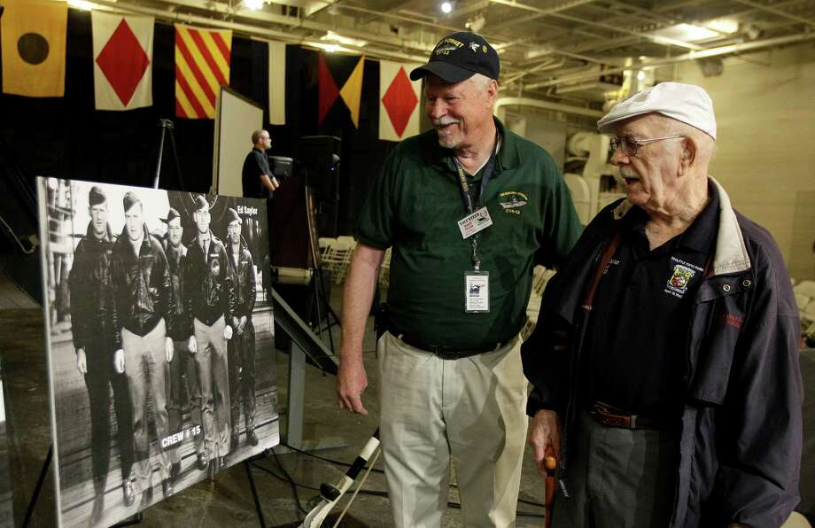 "Lt. Col. Edward Saylor, right, and USS Hornet volunteer Roger Felton look at an old photograph of ""Doolittle's Raiders"" on Saturday. Photo: Jeff Chiu / AP"