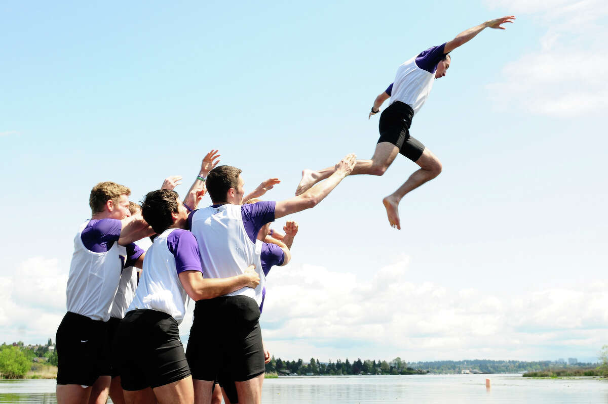 The University of Washington men's varsity team celebrates by throwing cosxswain Sam Ojserkis off the dock after winning the men's Windermere Cup.