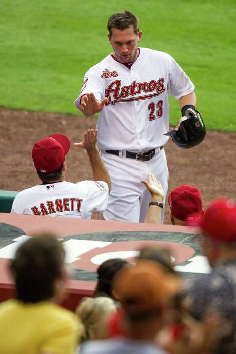 Chris Johnson (23), who hit a grand slam in the first inning, earns high-fives from the Astros' dugout after scoring on Justin Maxwell's double in the fourth. Photo: Smiley N. Pool / © 2012  Smiley N. Pool