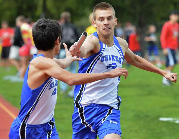 Shaker's Dan Ruiz, left, takes the baton from teammate Dan Phillips during the 4x800 at the Colonie
