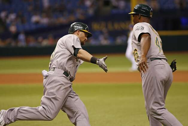 Oakland Athletics Jonny Gomes reaches his hand out to Tye Waller after hitting the game winning home run in the 12th inning against the Tampa Bay Rays of a baseball game, Saturday, May 5, 2012, in St. Petersburg, Fla. Photo: Scott Iskowitz, Associated Press