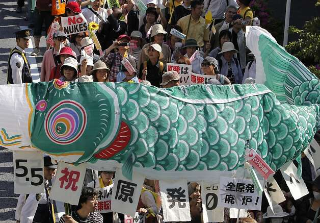 "Participants hold a traditional ""Koinobori"" carp-shaped banner for Children's Day during a march protesting against the usage of nuclear energy in Tokyo Saturday, May 5, 2012. Thousands of Japanese marched to celebrate the last of this nation's 50 nuclear reactors switching off Saturday, shaking banners shaped as giant fish that have become a potent anti-nuclear symbol. Photo: Itsuo Inouye, Associated Press"