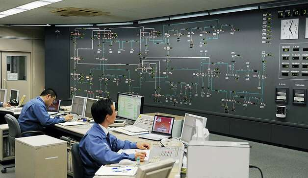 Hokkaido Electric Power Co. technicians monitor operations of their power plants in the central power supply control center at the utility's headquarters in Sapporo, northern Japan, Saturday evening, May 5, 2012. No. 3 unit of Tomari Nuclear Power Plant operated by the company, Japan's last operating commercial nuclear reactor, is set to go offline Saturday night for mandatory routine maintenance, leaving the nation without atomic-generated electricity for the first time in 42 years in the wake of the quake-triggered Fukushima nuclear crisis 14 months ago. (AP Photo/Kyodo News) Photo: Associated Press