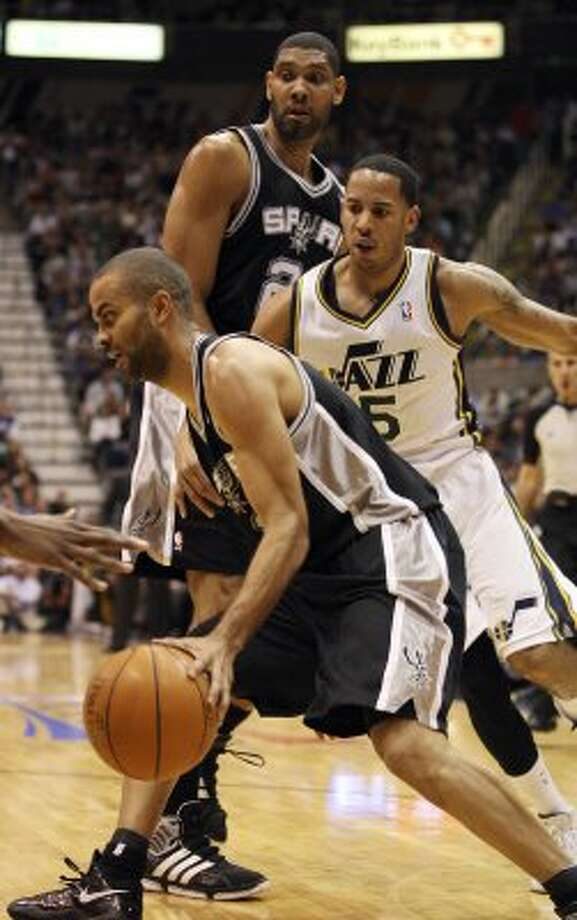 The Spurs'  Tony Parker looks for room around the Jazz's Devin Harris as Tim Duncan looks on in the first half of game three of the Western Conference first round at EnergySolutions Arena in Salt Lake City,  Saturday, May 5, 2012.  Jerry Lara/San Antonio Express-News (Jerry Lara / San Antonio Express-News)