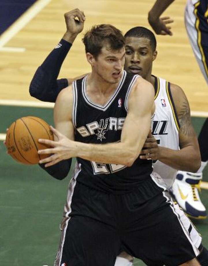 The Spurs'  Tiago Splitter looks to pass against the Jazz's Derrick Favors during second half action of Game 3 of the Western Conference first round Saturday May 5, 2012 at EnergySolutions Arena in Salt Lake City, Utah. The Spurs won 102-90. EDWARD A. ORNELAS/SAN ANTONIO EXPRESS-NEWS (EDWARD A. ORNELAS / SAN ANTONIO EXPRESS-NEWS)