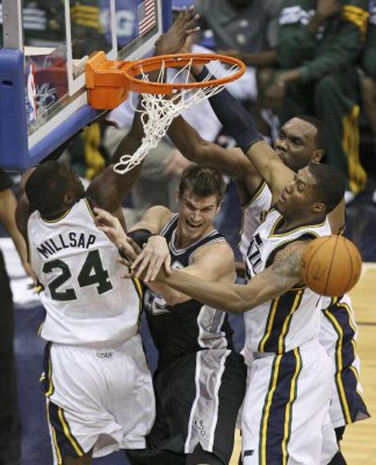 The Spurs'  Tiago Splitter passes between the Jazz's Paul Millsap,  Al Jefferson, and Derrick Favors during second half action of Game 3 of the Western Conference first round Saturday May 5, 2012 at EnergySolutions Arena in Salt Lake City, Utah. The Spurs won 102-90. EDWARD A. ORNELAS/SAN ANTONIO EXPRESS-NEWS (EDWARD A. ORNELAS / SAN ANTONIO EXPRESS-NEWS)