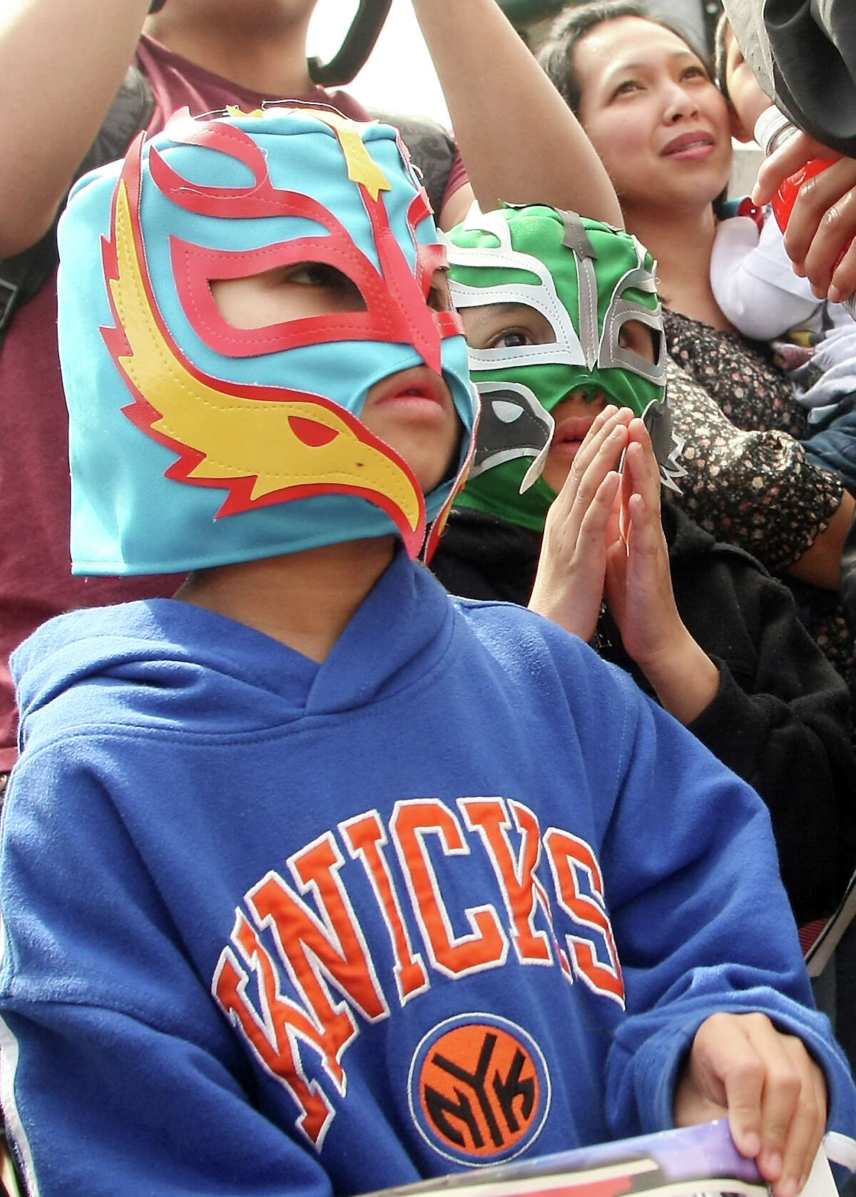 Wearing their traditional Lucha Libre masks, Cedric Quindo, 7, and Gavin Alasagas, 6, watch the wrestling match in the parking lot of La Poblanita restaurant during the Cinco de Mayo Street Fair in Bremerton, Wash. on Saturday May 5, 2012.