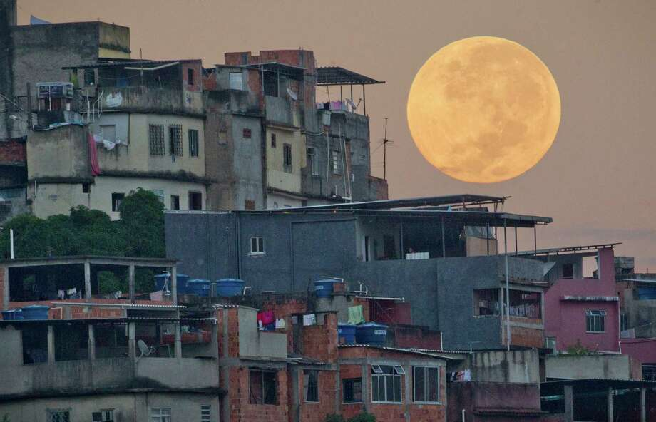 "The ""supermoon"" appears behind the Mare shanty town complex in Rio de Janeiro, Sunday, May 6, 2012. The moon was the closest it will get to the Earth this year _ and appeared 14 percent larger because of that. At its peak it was about 221,802 miles from Earth. (AP Photo/Victor R. Caivano) Photo: Victor R. Caivano, Associated Press / Copyright 2012 The Associated Press. All rights reserved. This material may not be published, broadcast, rewritten or redistribu"