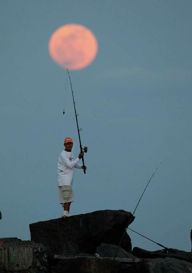 "A fisherman casts a line from a jetty as the ""supermoon""  appears over the Atlantic Ocean, Saturday, May 5, 2012, near Bal Harbour, Fla. The moon was the closest it will get to the Earth this year _ and appeared 14 percent larger because of that. At its peak it was about 221,802 miles from Earth. (AP Photo/Wilfredo Lee) Photo: Wilfredo Lee, Associated Press / Copyright 2012 The Associated Press. All rights reserved. This material may not be published, broadcast, rewritten or redistribu"