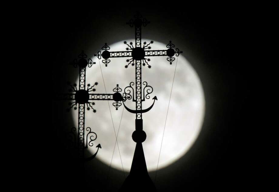 "The ""supermoon"" appears behind a steeple with crosses of an Orthodox church in the town of Novogrudok, 150 km (93 miles) west of Minsk, Belarus, late Saturday, May 5, 2012. The moon was the closest it will get to the Earth this year _ and appeared 14 percent larger because of that. At its peak it was about 221,802 miles from Earth.  (AP Photo/Sergei Grits) Photo: Sergei Grits, Associated Press / Copyright 2012 The Associated Press. All rights reserved. This material may not be published, broadcast, rewritten or redistribu"