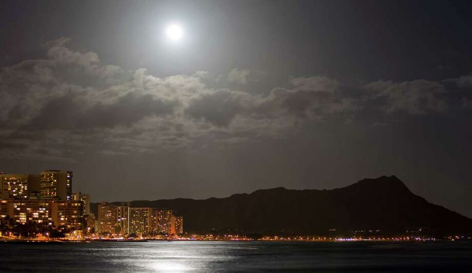 """A supermoon lights up Waikiki and Diamond Head Saturday, May 5, 2012, in Honolulu. A """"supermoon"""" event happens when the moon is closest to the earth therefore the biggest and brightest full moon of the year. (AP Photo/Eugene Tanner) Photo: Eugene Tanner, Associated Press / Associated Press"""