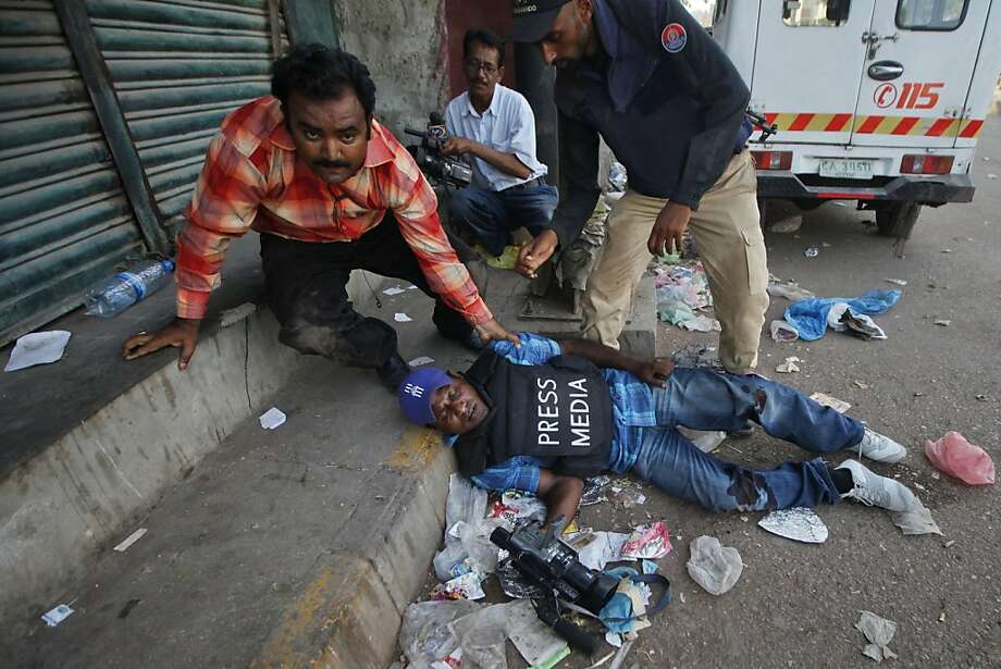 An injured cameraman is being attended to during a fire fight between police and gang members near Karachi's Lyari area April 29, 2012. At least 20 people including four police officials have been killed and 55 were injured during the last three days in the exchange of fire between police and gang members, local media reported.  REUTERS/Athar Hussain (PAKISTAN - Tags: POLITICS CIVIL UNREST CRIME LAW MEDIA) (Newscom TagID: rtrlfive211097) [Photo via Newscom] Photo: Athar Hussain, Reuters