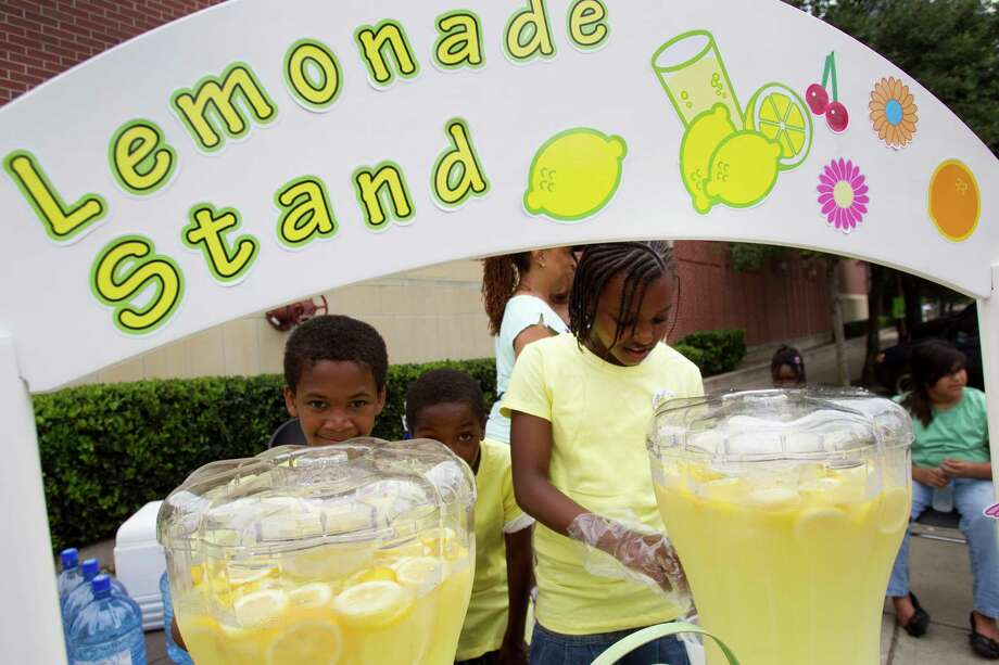 Ke'shawna Curtis, right, pours a glass of lemonade at the Clayton Homes stand during Lemonade Day Sunday, May 6, 2012, in Houston. Youths from across the city set up lemonade stands, to learn how to start, own and operate their own business. The children were working to raise money for a community center at Clayton Homes. Photo: Brett Coomer, Houston Chronicle / © 2012 Houston Chronicle