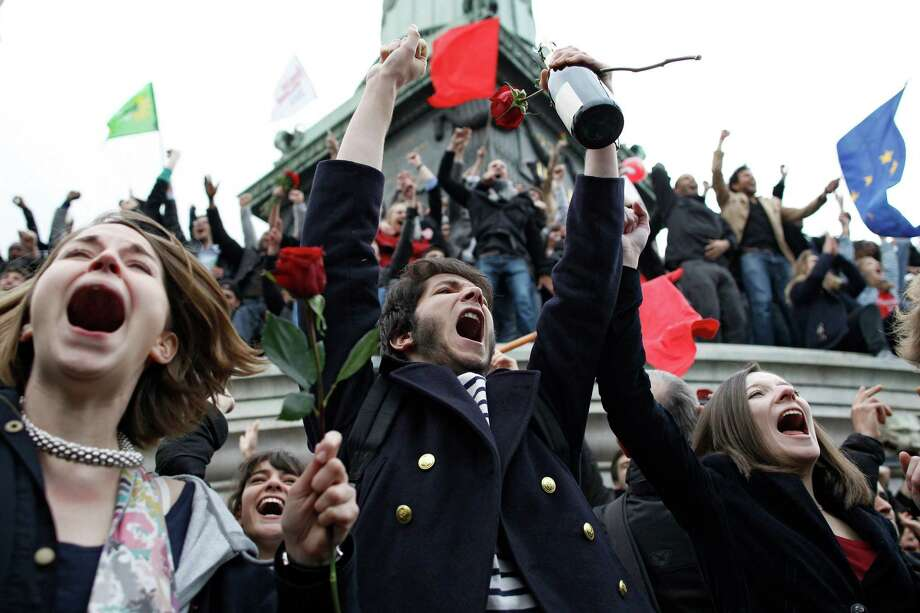 Supporters of Socialist Party candidate for the presidential election Francois Hollande react after the first results of the second round of French presidential elections were announced at Bastille Square in Paris, France, Sunday, May 6, 2012. Socialist Francois Hollande defeated conservative incumbent Nicolas Sarkozy on Sunday to become France's next president, heralding a change in how Europe tackles its debt crisis and how France flexes its military and diplomatic muscle around the world. Photo: Laurent Cipriani, Associated Press / Copyright 2012 The Associated Press. All rights reserved. This material may not be published, broadcast, rewritten or redistribu