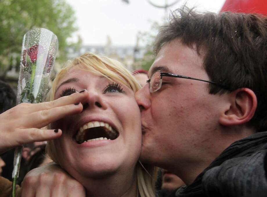 Two supporters of Socialist Party candidate for the 2012 French presidential election celebrate on May 6, 2012 outside the party's headquarters in Paris, following the announcement of the estimated results of the second round of presidential election. Francois Hollande was elected France's first Socialist president in nearly two decades on May 6, dealing a humiliating defeat to incumbent Nicolas Sarkozy and shaking up European politics. Photo: KENZO TRIBOUILLARD, AFP/Getty Images / AFP PHOTO