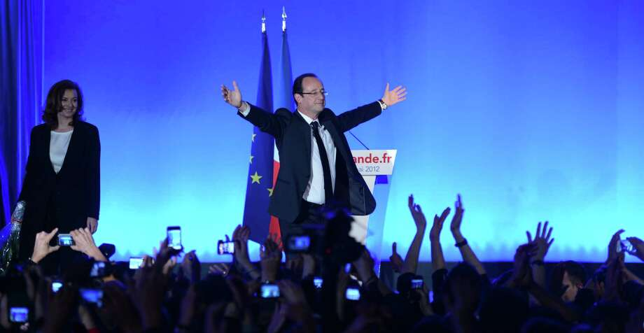 Socialist Party newly elected president Francois Hollande waves as his companion Valerie Trierweiler looks on after given a speech after the results of the second round of the presidential election on May 6, 2012 in Tulle, southwestern France. Francois Hollande was elected France's first Socialist president in nearly two decades today, dealing a humiliating defeat to incumbent Nicolas Sarkozy and shaking up European politics. Photo: PHILIPPE DESMAZES, AFP/Getty Images / AFP