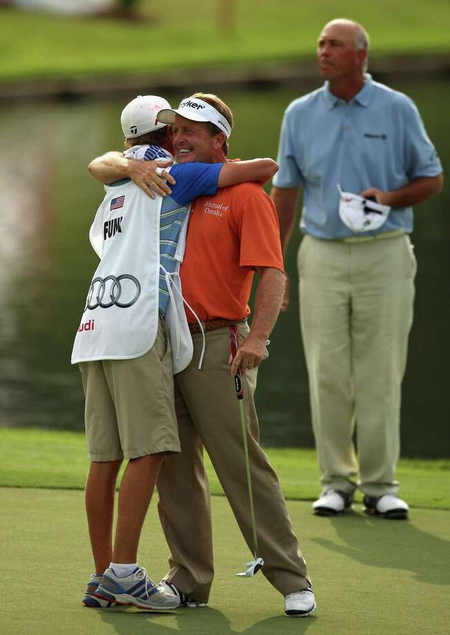 Fred Funk (center) hugs caddie and son Taylor as runner-up Tom Lehman looks on after winning the Insperity Championship, Sunday, May 6, 2012 at the Tournament Course in The Woodlands, TX. Funk finished at 14-under par. Photo: Eric Christian Smith, For The Chronicle