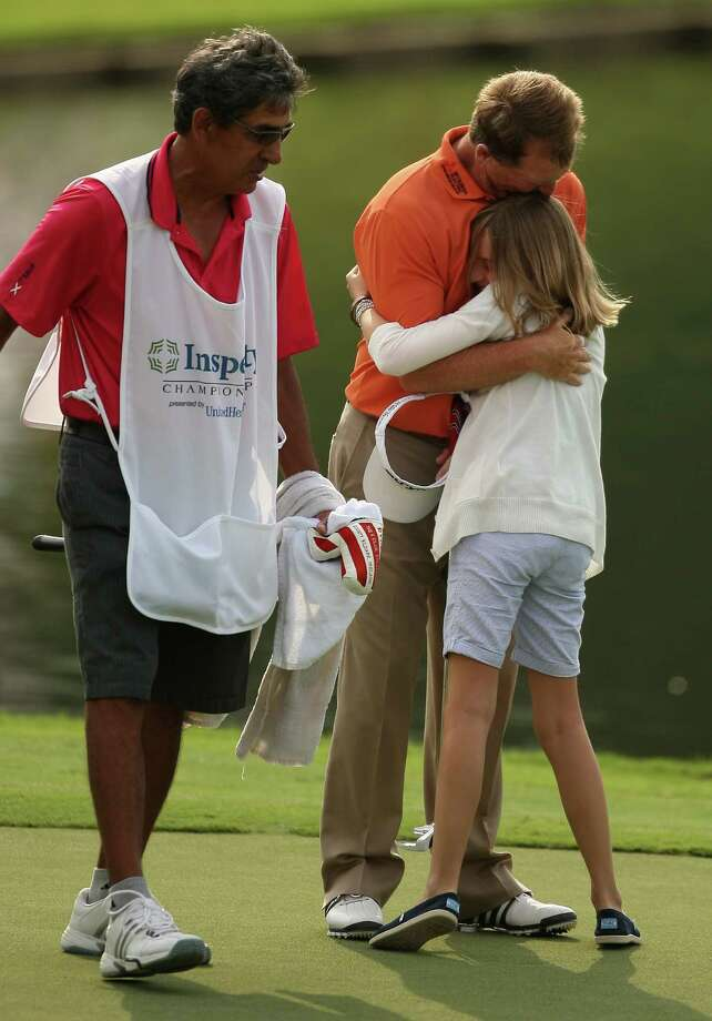Fred Funk (center) hugs daughter Perry, 12, as Tom Lehman's caddie Andrew Martiez looks on after Funk won the Insperity Championship, Sunday, May 6, 2012 at the Tournament Course in The Woodlands, TX. Photo: Eric Christian Smith, For The Chronicle