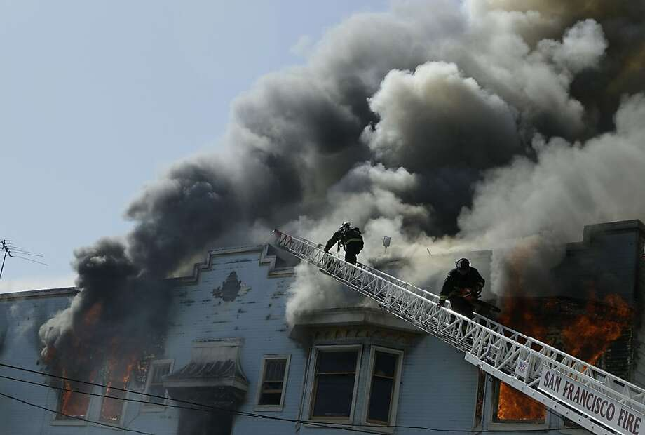 San Francisco firefighters battle a four-alarm fire at a residential and commercial building on the corner of Valencia Street and Duboce Avenue in San Francisco, Sunday, May 6, 2012. (AP Photo/Jeff Chiu) Photo: Jeff Chiu, Associated Press