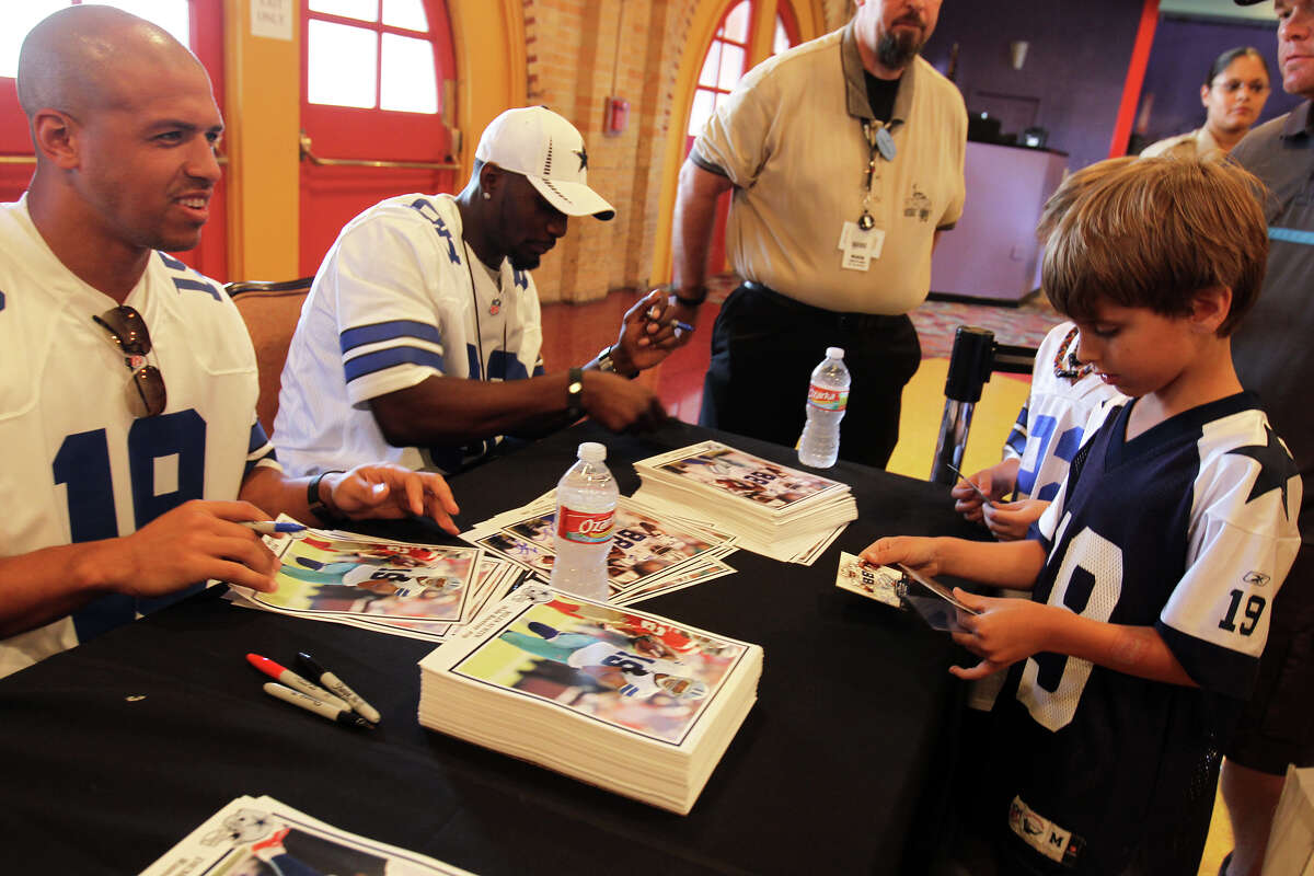 Miles Austin signs his player card for Andrew Knebel, 7, during Cowboys Fan Fest at Sunset Station, Sunday, May 6, 2012.