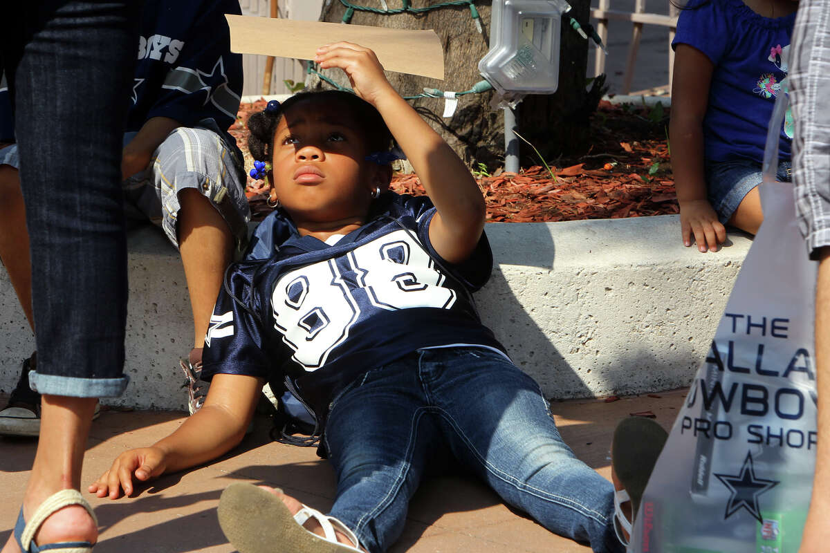 Detrinell Daniels, 8, lays on the ground shading her face with a sign in the line to get players' autographs at Cowboys Fan Fest at Sunset Station, Sunday, May 6, 2012.