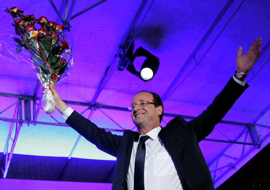 President-elect Francois Hollande holds a bouquet of roses after delivering his speech in Tulle, central France, Sunday, May 6, 2012.  Hollande defeated Nicolas Sarkozy to become France's next president. Sarkozy conceded defeat minutes after the polls closed. (AP Photo/Christophe Ena) Photo: Christophe Ena / Copyright 2012 The Associated Press. All rights reserved. This material may not be published, broadcast, rewritten or redistribu
