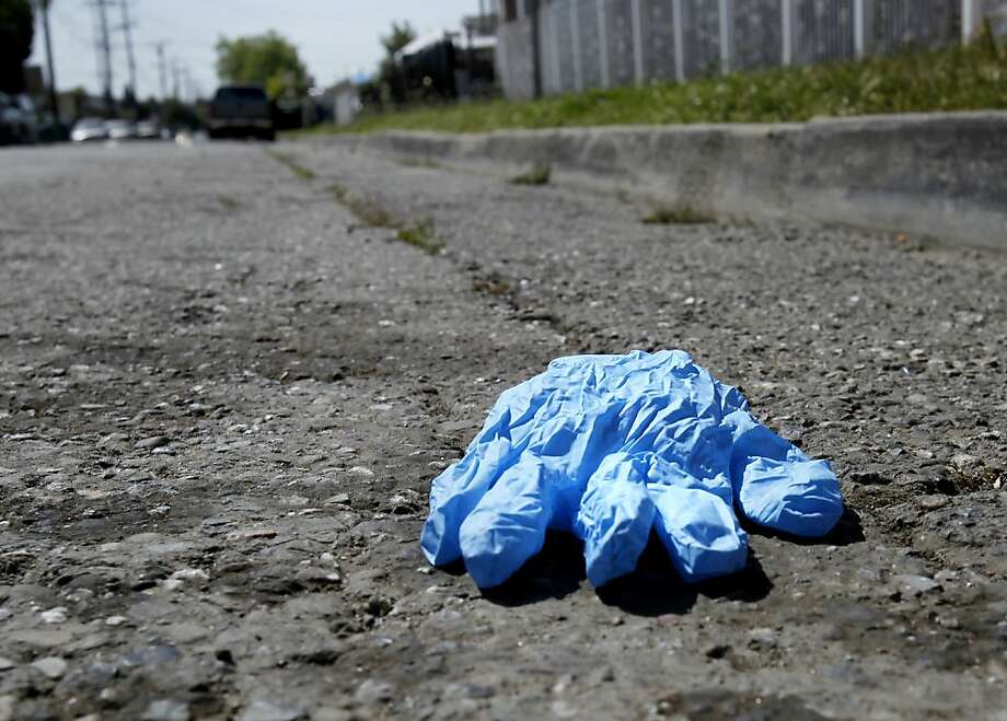 A paramedics glove lays on Birch Street at the scene of the shooting. A shootout that erupted near 92nd Avenue and Birch Streets in Oakland, Calif. wounded an Oakland policeman and killed the suspect Sunday May 6, 2012. Photo: Brant Ward, The Chronicle