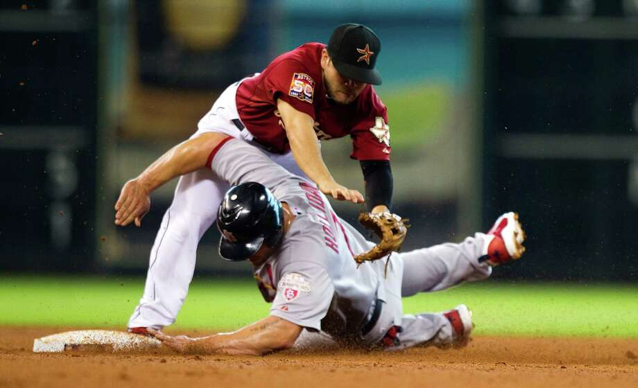 Astros second baseman Jose Altuve can't avoid getting roughed up by onetime Oklahoma State football signee Matt Holliday while turning a double play in the fifth inning. Photo: Brett Coomer / © 2012 Houston Chronicle