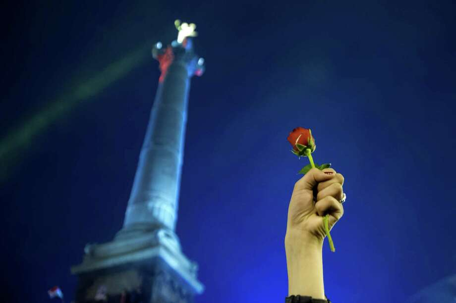 A supporter of France's Socialist Party  newly elected president Francois Hollande  holds a rose as he celebrates at the Bastille Square in Paris on May 6, 2012 after the announcement of the results of the French presidential final round. Hollande was elected France's first Socialist president in nearly two decades on Sunday, dealing a humiliating defeat to incumbent Nicolas Sarkozy and shaking up European politics. Photo: BERTRAND LANGLOIS, AFP/Getty Images / BERTRAND LANGLOIS