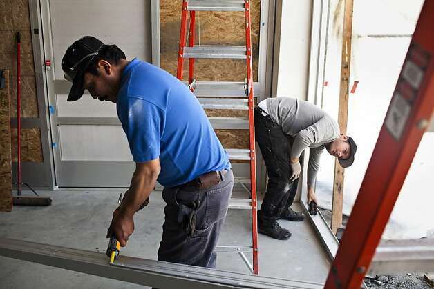 Dan Casey, right, and Raul Ayala, left, of KC Glass, work on the construction of a new Walgreens store on the corner of Jones and Bay Streets in San Francisco, Calif., Thursday, April 26, 2012. The pharmacy chain store is under construction in the location of the old Tower Records store near Fisherman's Wharf, a spot that's two blocks from not one, but two, other Walgreens. There are the eight within a mile-and-a-half radius and 67 total in San Francisco.  Jason Henry/Special to The Chronicle Photo: Jason Henry, Special To The Chronicle