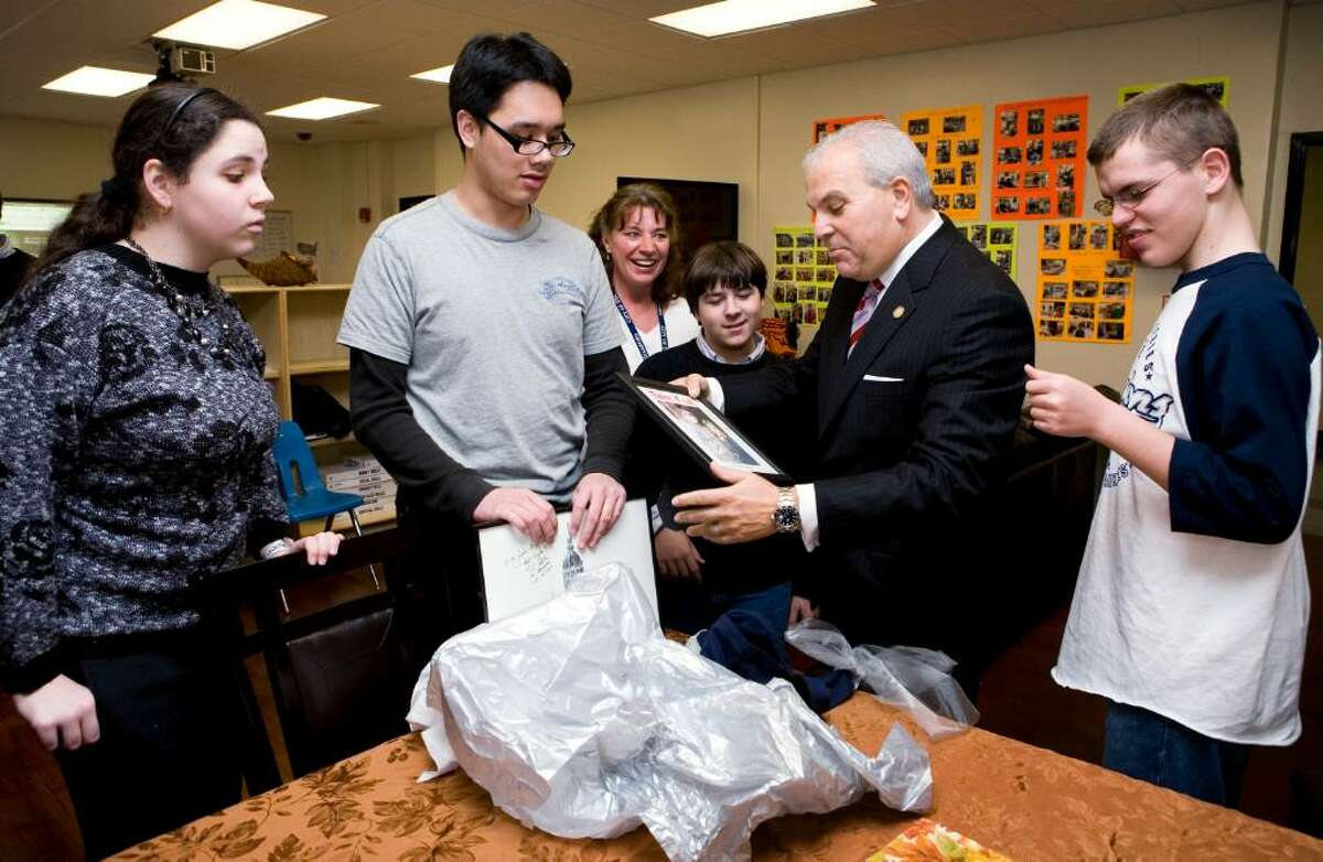 Lt. Gov. Michael Fedele, second from right, is presented with a gift by Stamford High School students Olivia Shea, left, Arrian Velasco, second from left, Anthony Portanova, center, and Mickey Teuburt, right. Their teacher, Sheree Cook, looks over their shoulders, third from left. Fedele was at the school to visit a new, specially designed Autism Disorder Spectrum classroom.