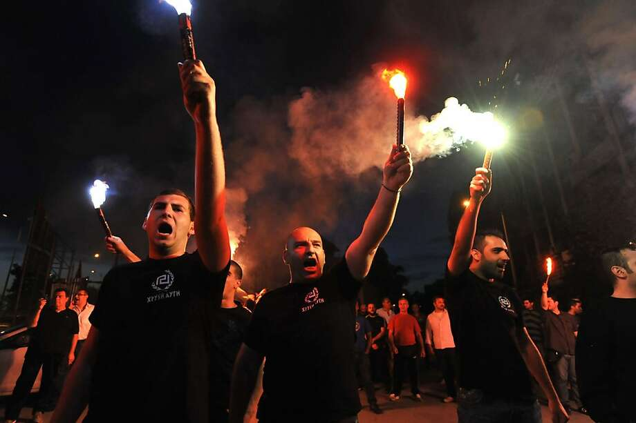 Extreme far-right Golden Dawn party's supporters hold flares during the elections results in the northern Greek port city of Thessaloniki, Sunday, May 6, 2012. Golden Dawn, which has vowed to kick out immigrants and mine Greece's borders with Turkey, was predicted to win between 6.5-7.5 percent, well above the 3 percent needed to enter parliament. (AP Photo/Nikolas Giakoumidis) Photo: Nikolas Giakoumidis, Associated Press