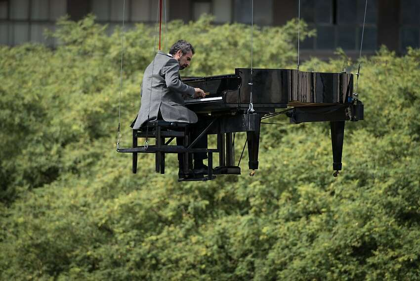 Brazilian pianist Ricardo de Castro Monteiro plays in the air on a piano hanging from wires during the annual