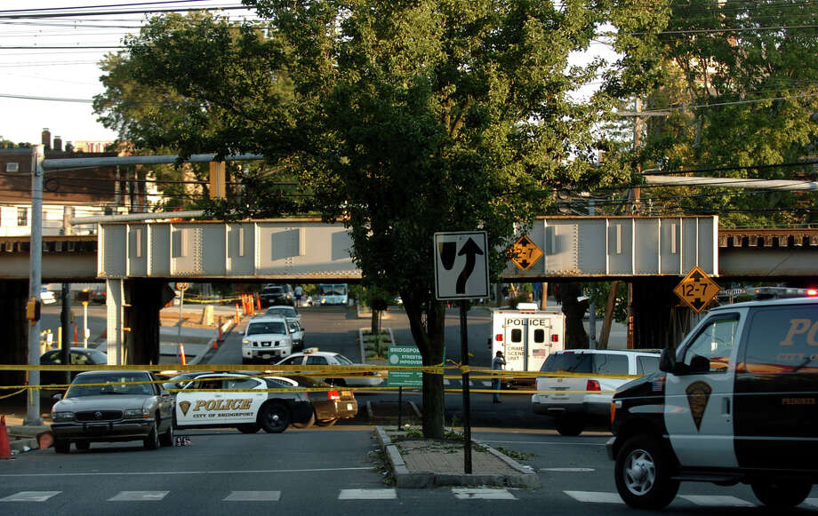 Police vehicles and a crime scene truck at the scene of a shooting which happened along Railroad Avenue and extended to Park Avenue in Bridgeport, Conn. on Thursday September 1, 2011. Quayman Crosby, 20, was killed in what police have called a gang-related incident. Photo: Christian Abraham / Connecticut Post