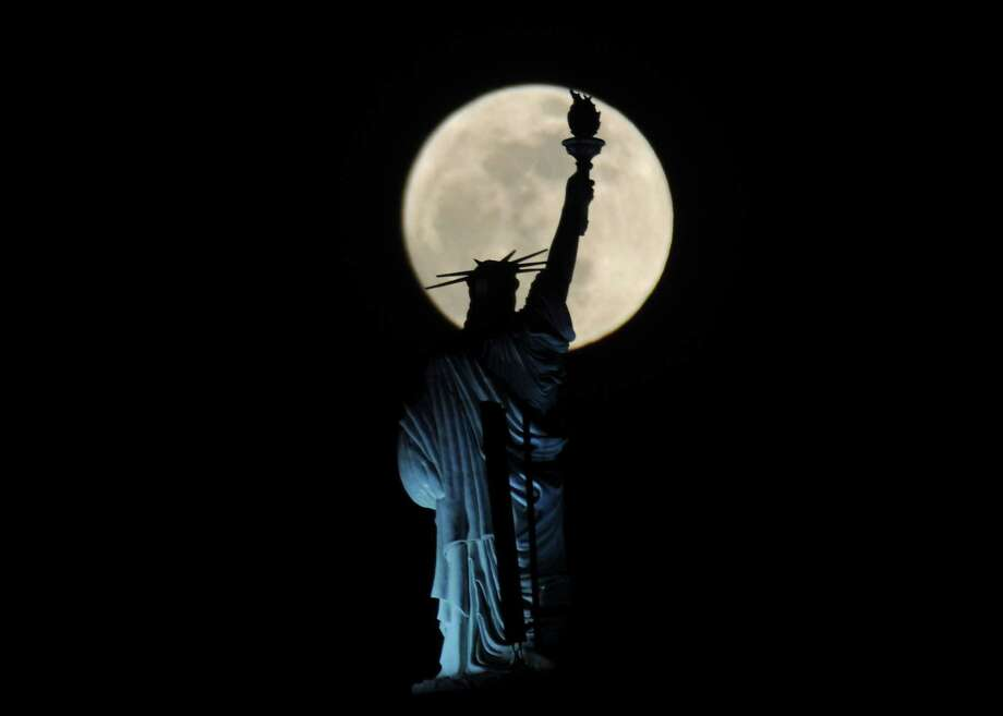 "The full moon rises behind Statue of Liberty replica atop of a hotel in Kosovo's capital Pristina on Saturday, May 5, 2012. On Saturday, the moon will be a ""supermoon"" or perigee moon as the moon is at it's closest approach to the earth. Photo: VISAR KRYEZIU, AP / AP"
