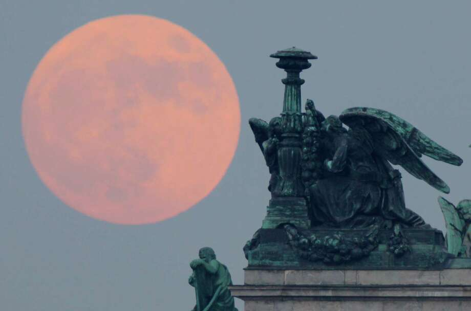 "The full moon rises behind statues of angels fixed at the St. Isaak's Cathedral in St.Petersburg, Russia, Saturday, May 5, 2012. Saturday's event is a ""supermoon,"" the closest and therefore the biggest and brightest full moon of the year. Photo: Dmitry Lovetsky, AP / AP"