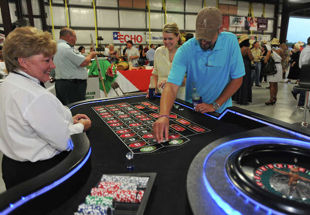 Jackie Mullins runs the roulette table for Josh Grammer and Jessica Grammer at the Cattle Barron's Ball on Saturday. With entertainment, food and casino games, the social event benefits the American Cancer Society. Photo taken Saturday, May 5, 2012 Guiseppe Barranco/The Enterprise Photo: Guiseppe Barranco, STAFF PHOTOGRAPHER / The Beaumont Enterprise