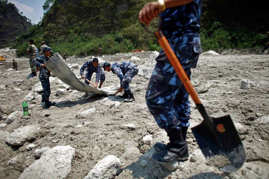 Nepalese rescuers search through mud and debris after a flash flood  in the Seti river at Kharapani village of Kaski district, about 200 kilometers (125 miles) west of capital Katmandu, Nepal, Monday, May 7, 2012. Rescuers searching through mud and debris for flash-flood victims in northwestern Nepal had found 17 bodies by Monday, police said. Another 47 people, including three Ukrainian tourists, were missing and presumed dead.(AP Photo/Niranjan Shrestha) Photo: Niranjan Shrestha, Associated Press / AP