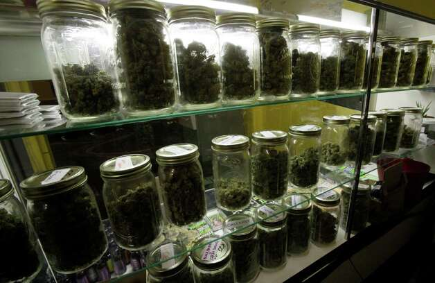 Traditional canning jars hold varieties of marijuana in a cabinet at the La Brea Collective medical marijuana dispensary in Los Angeles Tuesday, Nov. 17, 2009. Los Angeles County's district attorney says he intends to prosecute owners of marijuana dispensaries that take cash for pot. (AP Photo/Reed Saxon) Photo: Reed Saxon, ASSOCIATED PRESS / ASSOCIATED PRESS