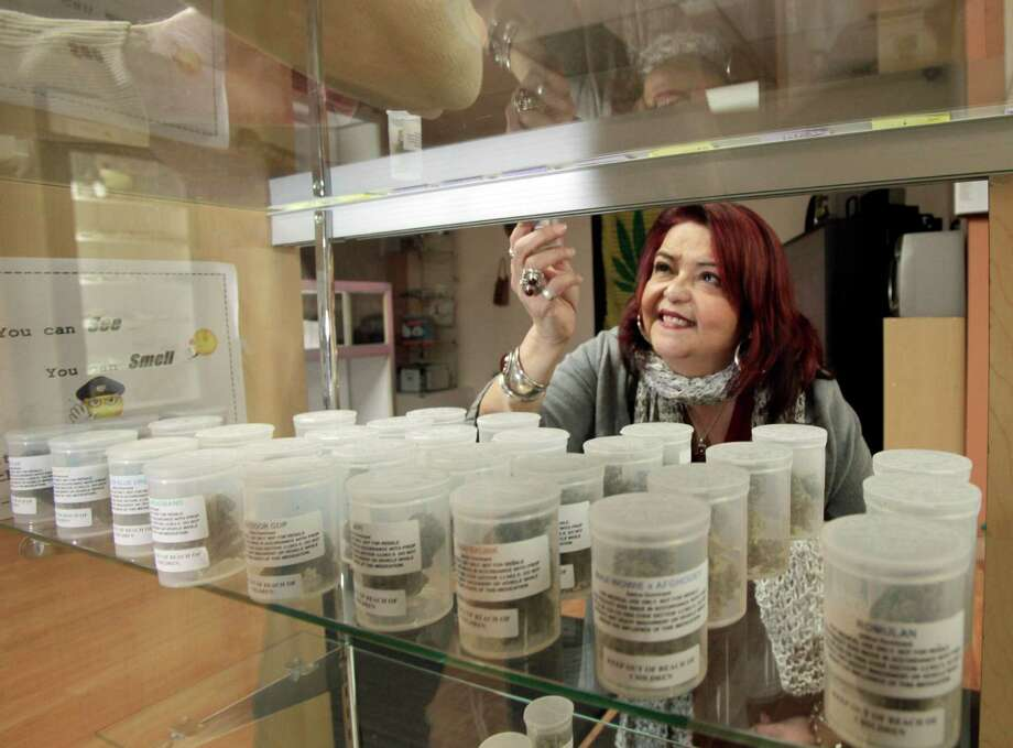 Yamileth Bolanos, who runs Pure Life Alternative Wellness Center, selects a vial of marijuana for a client at her store in Los Angeles Tuesday, Jan. 26, 2010.  The day feared by medical marijuana advocates arrived Tuesday when the City Council approved an ordinance intended to close hundreds of pot shops and banish those that remain to industrial areas.  Bolanos said she'll have to close her clinic to comply with the new restrictions, then reopen at a new location nine miles away.  The new law, which passed 9-3, caps the eventual number of dispensaries in the city at 70. (AP Photo/Reed Saxon) Photo: Reed Saxon, ASSOCIATED PRESS / ASSOCIATED PRESS