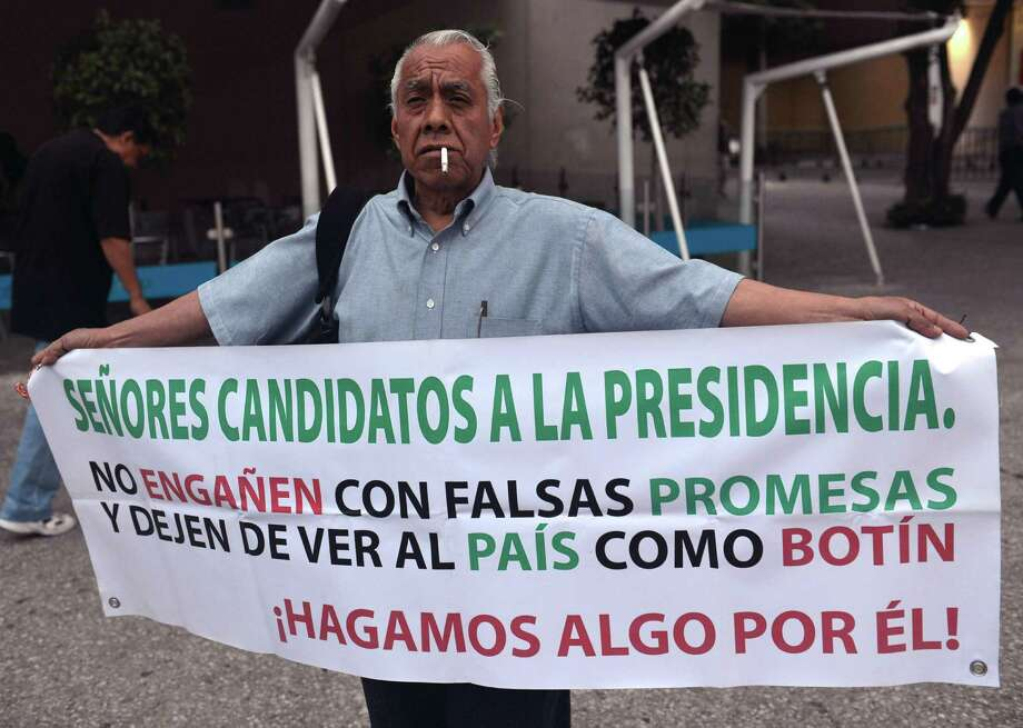 "A man shows a banner reading ""Candidates to the presidency, don' t fool with fake promises and stop seeing the country as a plunder. Let's make something for it!"", while arriving to the World Trade Center building in Mexico City, on May 6, 2012. Four presidential candidates will participe in the first debate promoted by the Federal Electoral Institute.  AFP PHOTO/ Yuri Cortez        (Photo credit should read YURI CORTEZ/AFP/GettyImages) Photo: YURI CORTEZ, Getty Images / 2012 AFP"