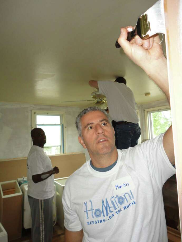 Martin Magida of Darien paints a living room wall in the house of Norwalk homeowner Diana Maurice Saturday, while Josh Molaver of Norwalk and James Clark of Bridgeport turn their attention to a ceiling fan. Photo: Contributed Photo